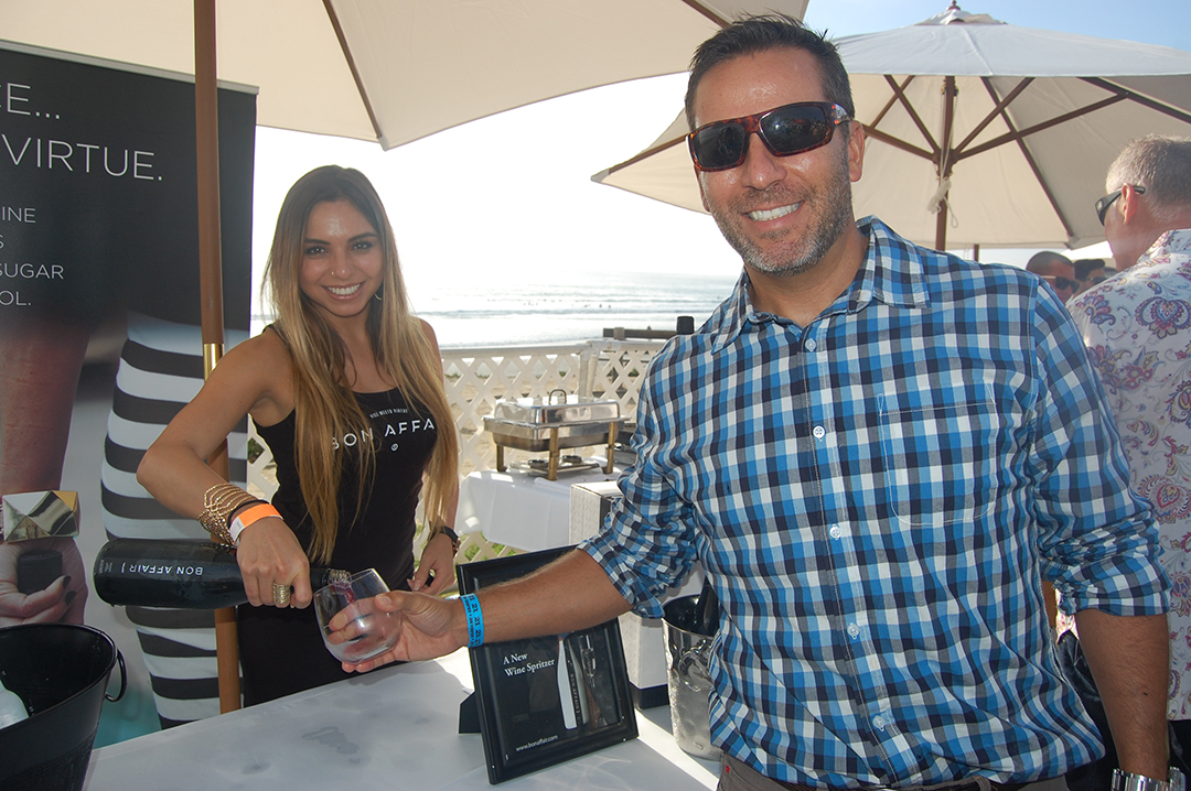 """Bianca Cruz-Leonardo pours Jonathan Friedman from Carmel Valley a sample of Bon Affair, a wine spritzer that was featured on """"Shark Tank"""" and created by a Solana Beach resident. Photo by Bianca Kaplanek"""