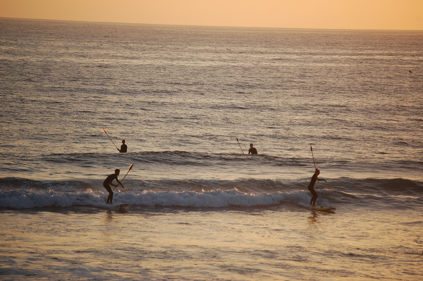 The evening ends at sunset with lifeguards surfing ashore carrying tiki torches. Photo by Bianca Kaplanek