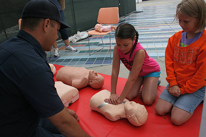 "Maddie Gray, 9, gives hands only CPR a try. The song ""Stayin' Alive"" by the BeeGeeshelped participants learn the correct rhythm to administer compressions. Photo by Promise Yee"