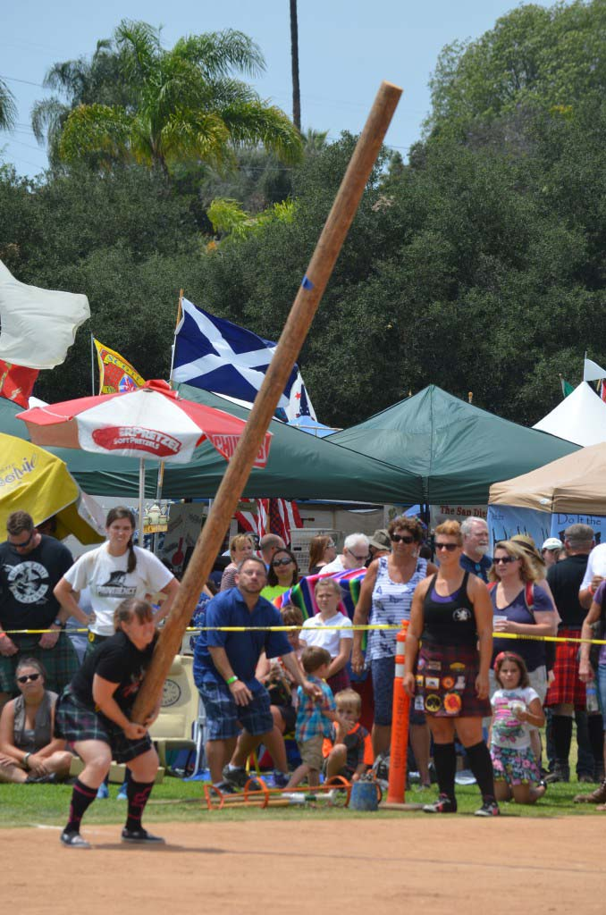 Crowds look on as athletes compete in the caber toss. Photo by Tony Cagala