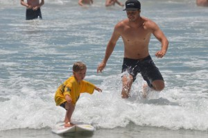 Surfer Nathaniel Curran gets his 4-year-old nephew Oliver ready for next year's Bro-Am surf contest. Photo by Tony Cagala