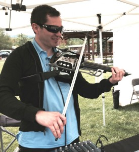 Musician Dave Villano from Denver entertains visitors at a craft fair in Grand Lake. His electric violin has a unique sound, and he invented the support strap that holds the violin to make the instrument ergonomically easier to play. Villano also is a master at the guitar, bass guitar, piano, Irish whistle and Uilleann pipes.