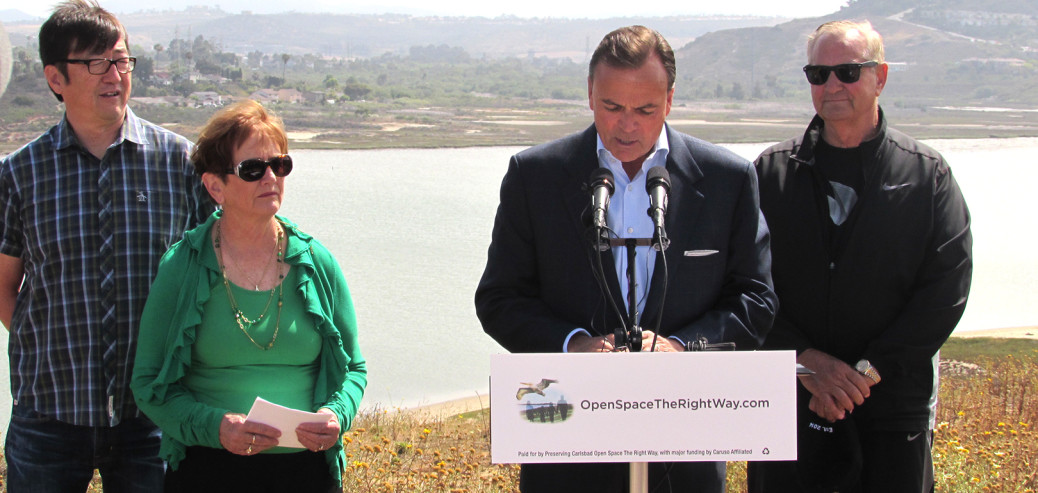 In May, Rick Caruso (at podium) announces plans to develop the current sight of the strawberry fields into an upscale shopping center anchored by a Nordstrom with the help of realtor Carlton Lund (far right), Carlsbad Strawberry Company Owner Jimmy Ukegawa (far left) and Agua Hedionda Lagoon Foundation President Maureen Simons.  File photo by Ellen Wright