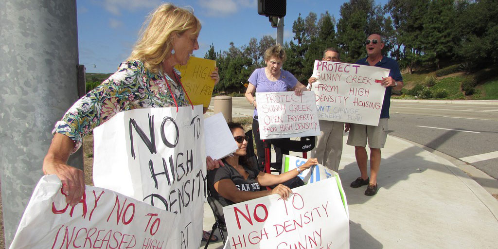 Some residents in Carlsbad protest high-density housing in the property on the corner of College Boulevard and El Camino Real on Wednesday. Photo by Ellen Wright