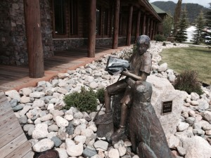 """Boy Reading to His Dog,"" installed in 2008, sits on the south side of the Juniper Library in Grand Lake's town park. The life-size bronze was created by Howard Neville. The artist had to walk the dog, a Lab named Pongo, for about an hour before each sitting so the dog would be tired enough to sit still for the artist."