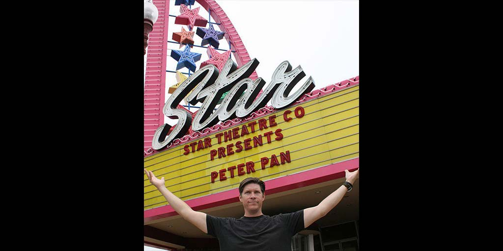 David Schulz, Star Theatre Company managing artistic director, in front of the restored neon sign. A dedication ceremony thanked donors on July 3. Photo by Promise Yee