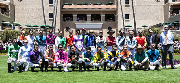 Jockeys pose for a group picture in the paddock prior to the first race of opening day at Del Mar racetrack. Photo by Bill Reilly