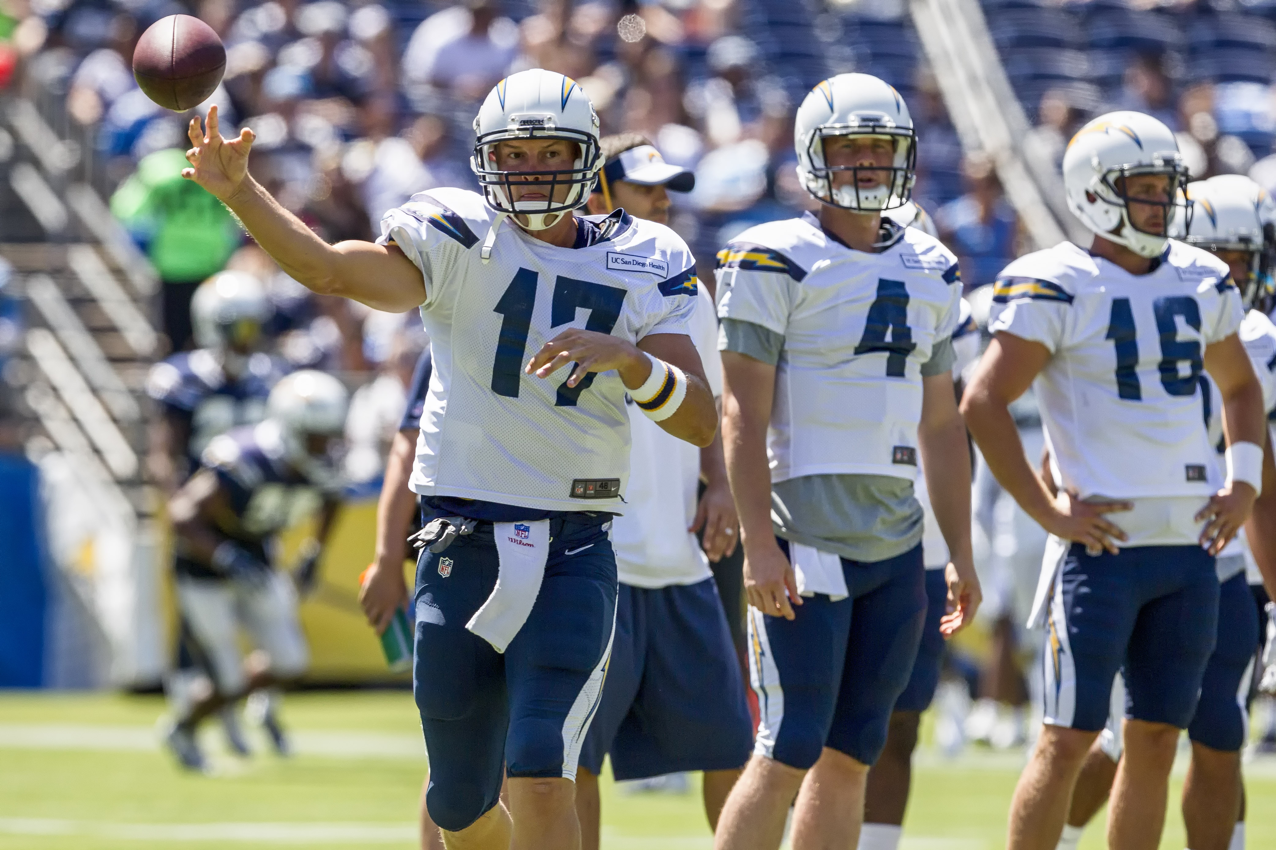 San Diego Chargers quarterback Philip Rivers (17) throws a pass downfield while backup quarterbacks Brad Sorensen (4) and Chase Rettig (16) observe during Fan Fest 2015. Photo by Bill Reilly