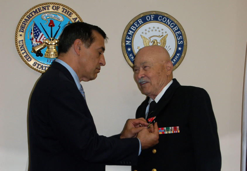 U.S. Rep. Darrell Issa pins the Bronze Star Medal on retired Navy Capt. Robert A. Sulit during an Aug. 17 ceremony at the congressman's Vista office. Photo by Bianca Kaplanek
