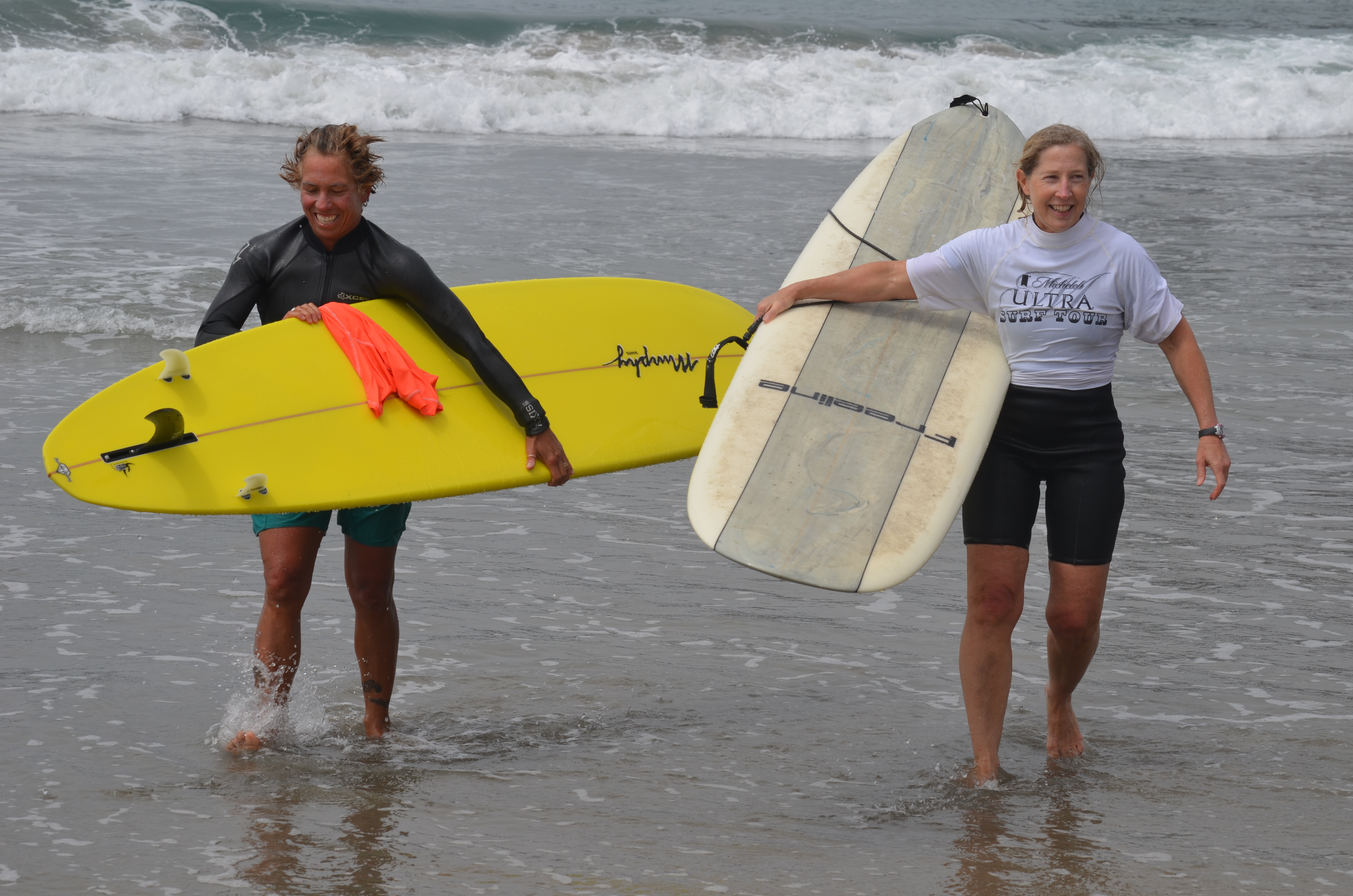 Lisa Carulli, left, and Karen Cochran emerge from the ocean following their heat at the Oceanside Longboard Surfing Club's annual surf competition on Sunday. Photo by Tony Cagala