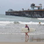Surfers finish their heat at the south side of the Oceanside Pier on Sunday under the watchful eye of a camera drone. Photo by Tony Cagala