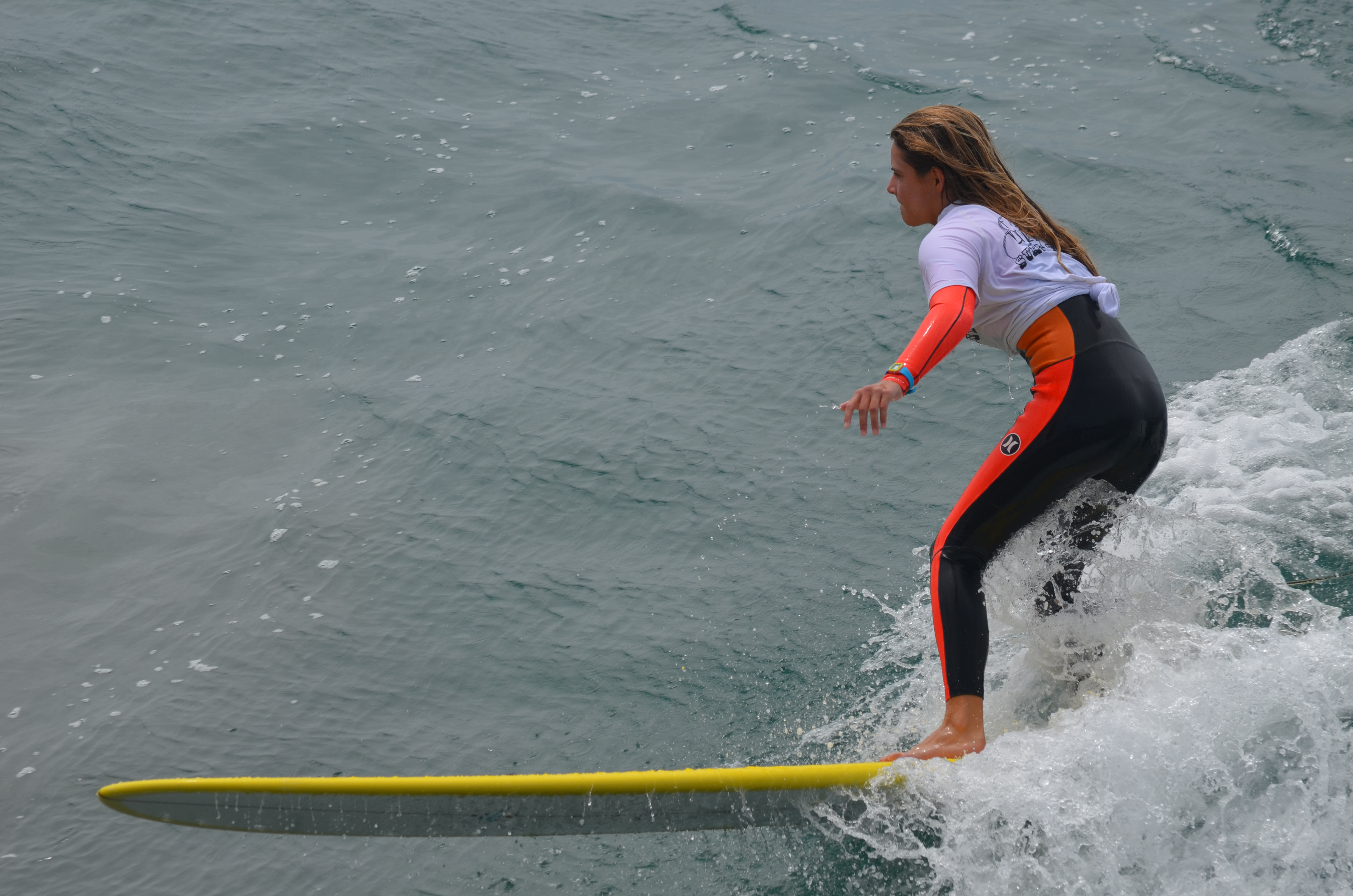 A competitor maneuvers her longboard along a wave on Sunday. Photo by Tony Cagala