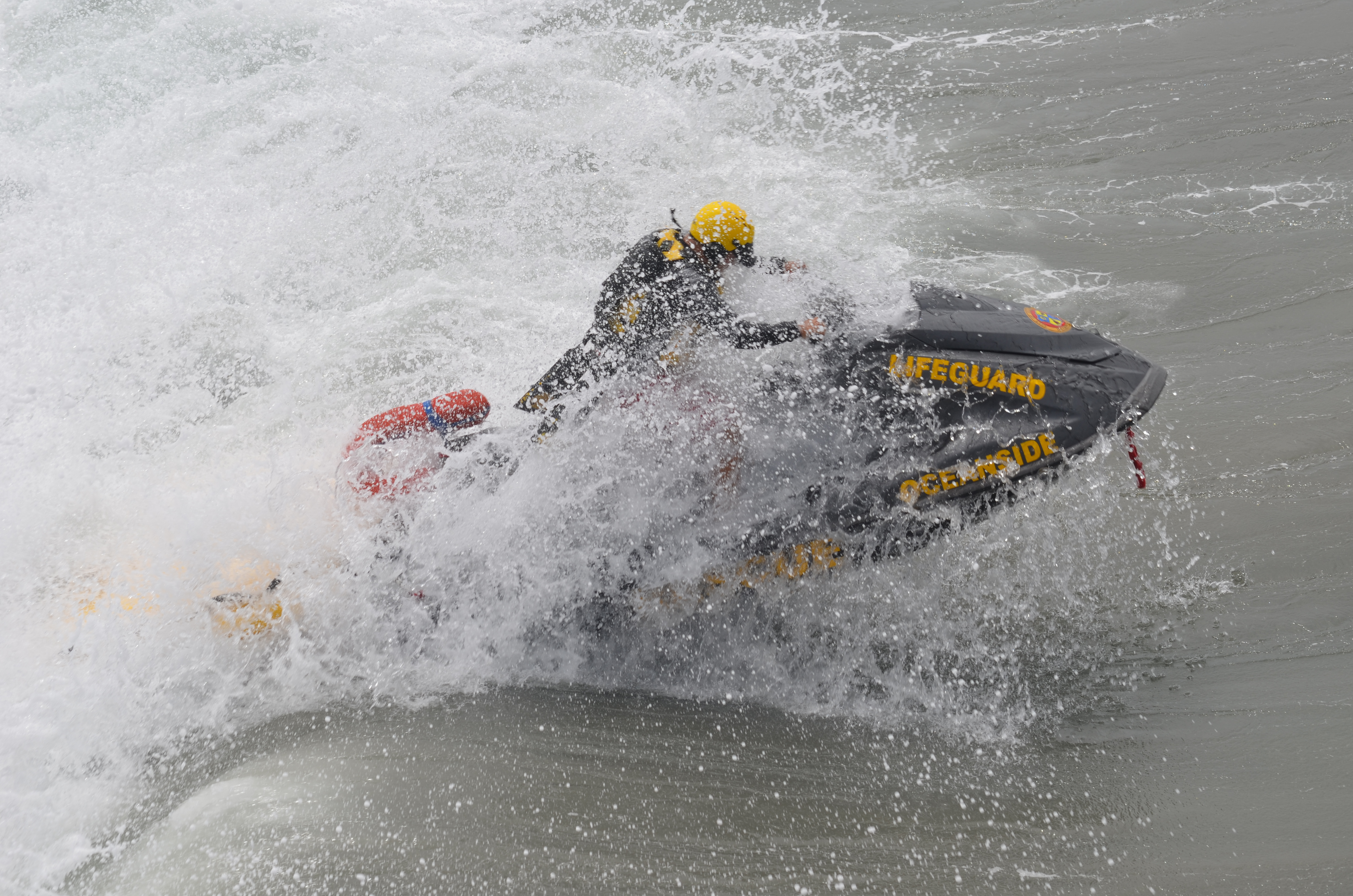 One of Oceanside's lifeguards powers through a wave on a jet ski on his way out to keep an eye on surfers and swimmers in the area. Photo by Tony Cagala