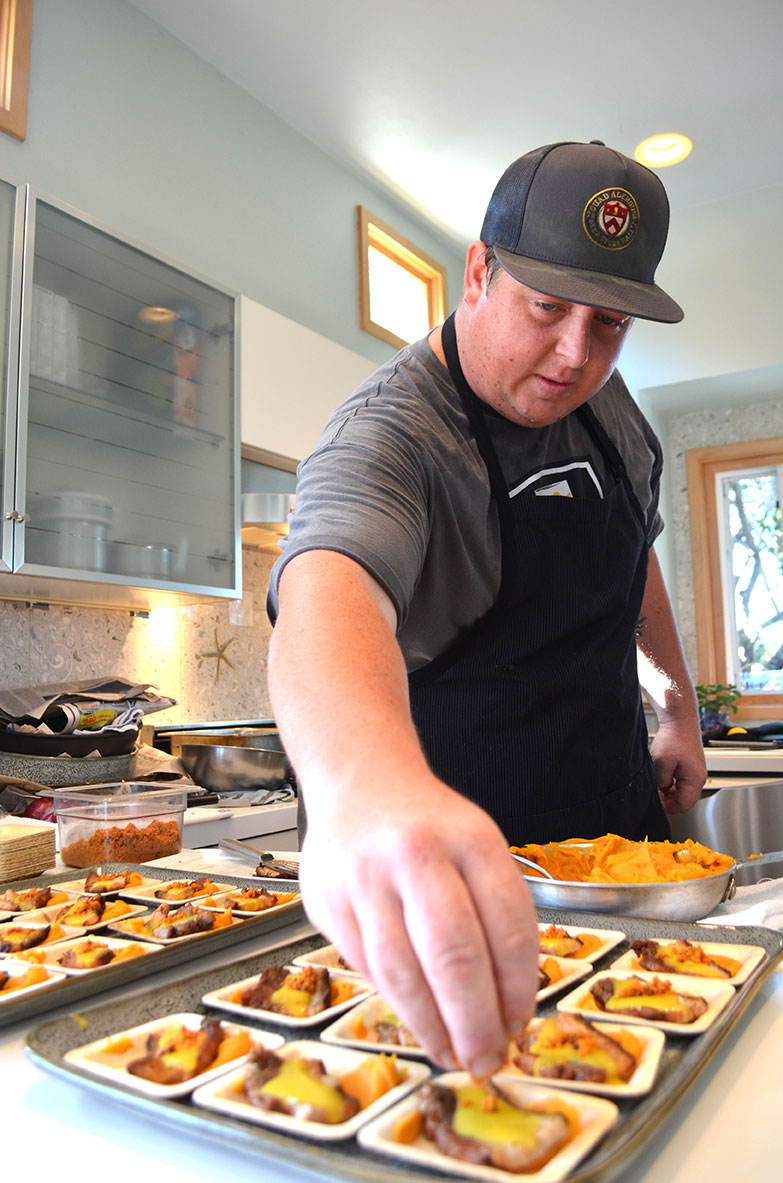 Chef Brandon Brooks of Quad Ale-House puts the finishing touches on some hickory smoked pork belly. Photo by Tony Cagala