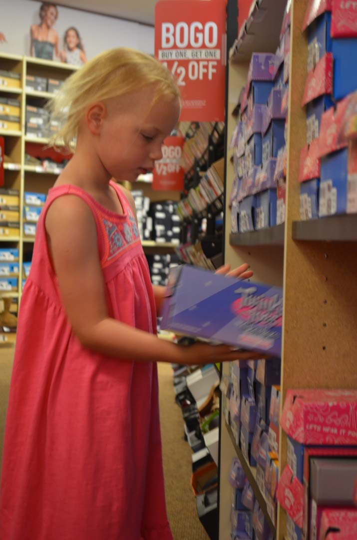 Sophie Lawler-Ehr, 8, looks over the selection of shoes to choose from. Photo by Tony Cagala