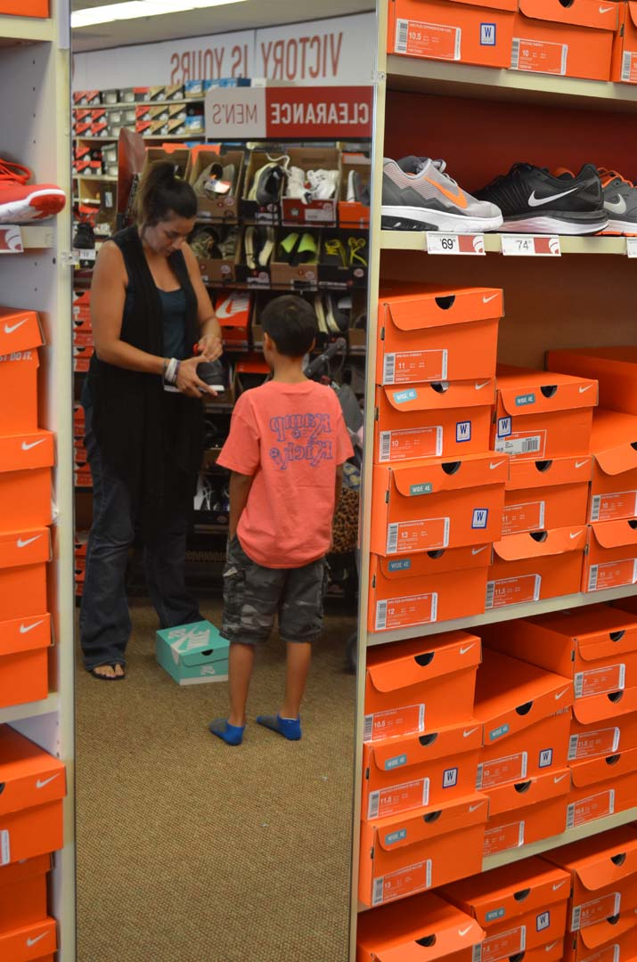 Alisha Shohab laces up a pair of new shoes for Shai Louie to try on. Photo by Tony Cagala
