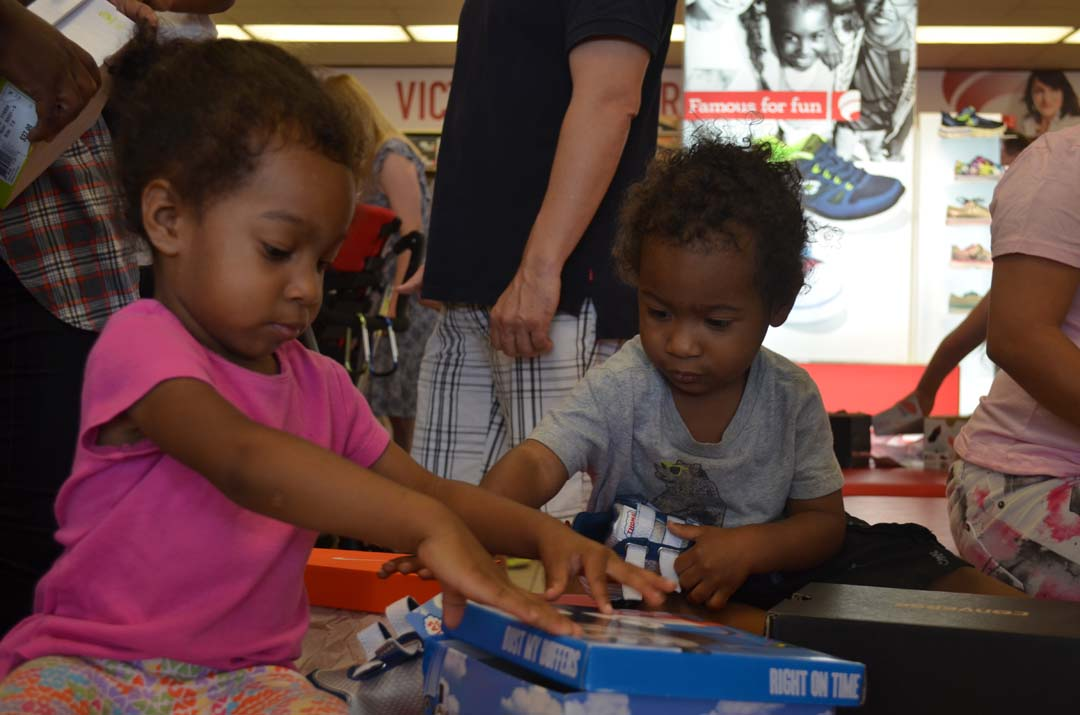 Tiarra Perry, left, and brother Treyvon Perry go through boxes of shoes to try on. Photo by Tony Cagala