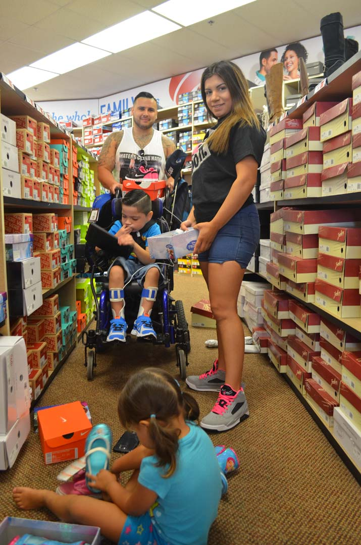 Jacob Wallis, Lucy Verde, Izaiah Wallis and Caliah Wallis find shoes and backpacks to get ready to go back to school. Photo by Tony Cagala