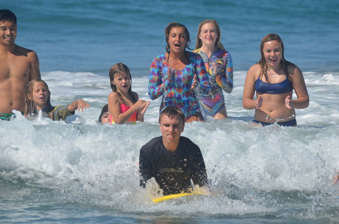 Levi Bressan, 16, gets cheers from volunteers and friends as he rides a wave at South Ponto Beach on Sunday. Photo by Tony Cagala