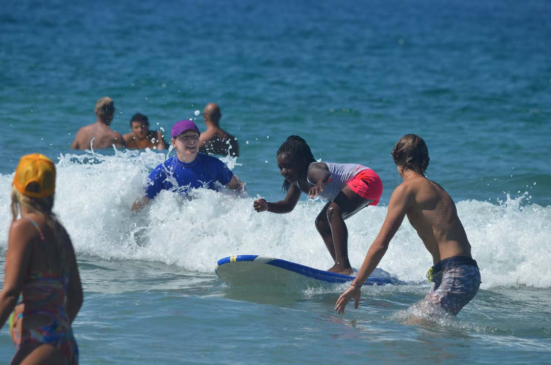 A young surfer catches a wave during Sunday's Encinitas Lions Club and Swami's Surfing Association's blind surfing event. Photo by Tony Cagala