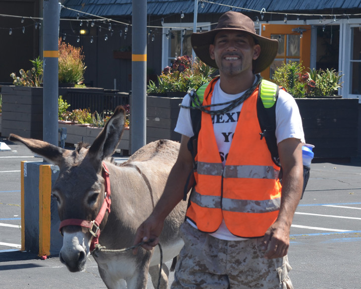 Rubén Ruíz Vega and his 4-year-old donkey Tocayo walk through Encinitas on Monday along the Coast Highway 101 on their way to Los Angeles. He's advocating for better human rights conditions and more opportunities in Mexico. Photo by Tony Cagala