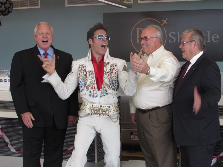 From left San Diego County Supervisor Bill Horn, an Elvis impersonator, Founder and CEO of BizAir Shuttle Dan Cretsinger and Carlsbad Mayor Matt Hall at the launching of the shuttle airline's first flight to Las Vegas on July 30. The airline announced this week that it has suspended all of its flights out of Carlsbad's McClellan-Palomar Airport. File photo by Ellen Wright