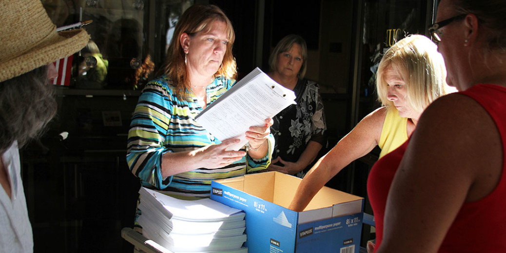 Assistant City Clerk Shelley Collins gathers referendum signatures submitted by a volunteer organization which is hoping for the chance to vote on the Agua Hedionda 85/15 Plan. Photo by Bryan Snyder