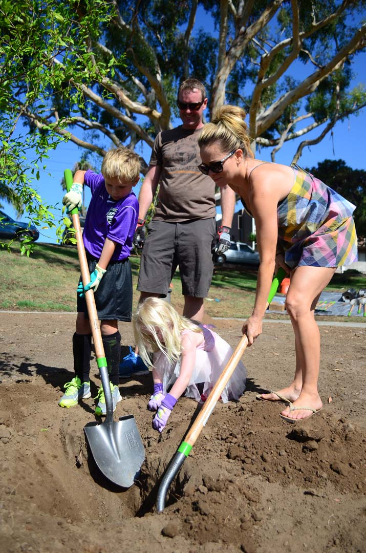 From left: Dexter Bullock, 6, Greg Bullock, Maunee Bullock and Eleanor Bullock, 4, help find a spot for a fruit tree. Photo by Tony Cagala