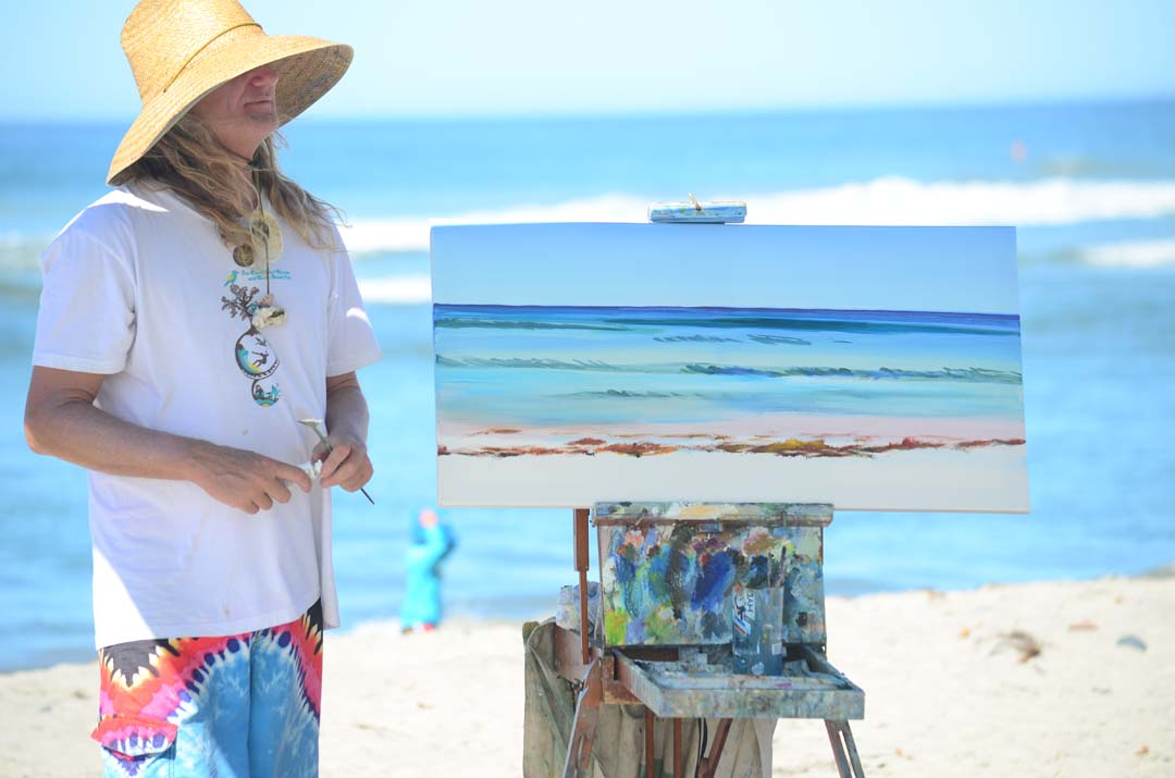 Artist Kevin Anderson paints a seascape during Saturday's event at Cardiff Reef. Photo by Tony Cagala