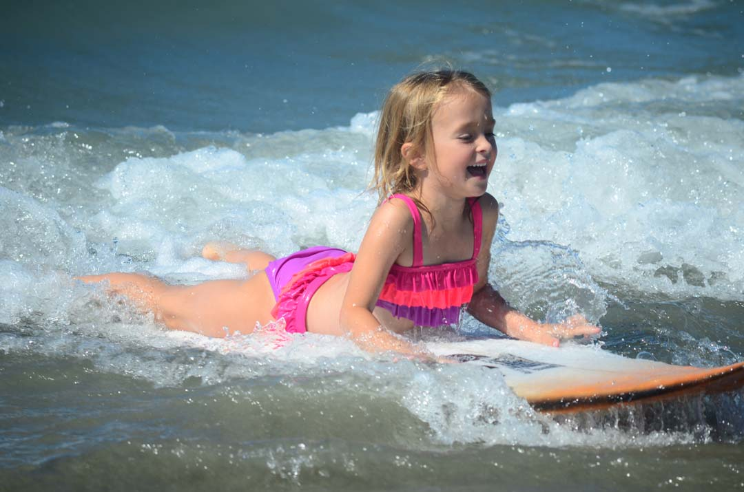 Grace Harrison, 5, has some fun riding a surfboard back to the beach. Photo by Tony Cagala