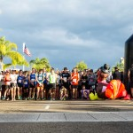 The American flag waves in the background as runners listen to the National Anthem prior to the start of the Encinitas Turkey Trot. Photo by Bill Reilly
