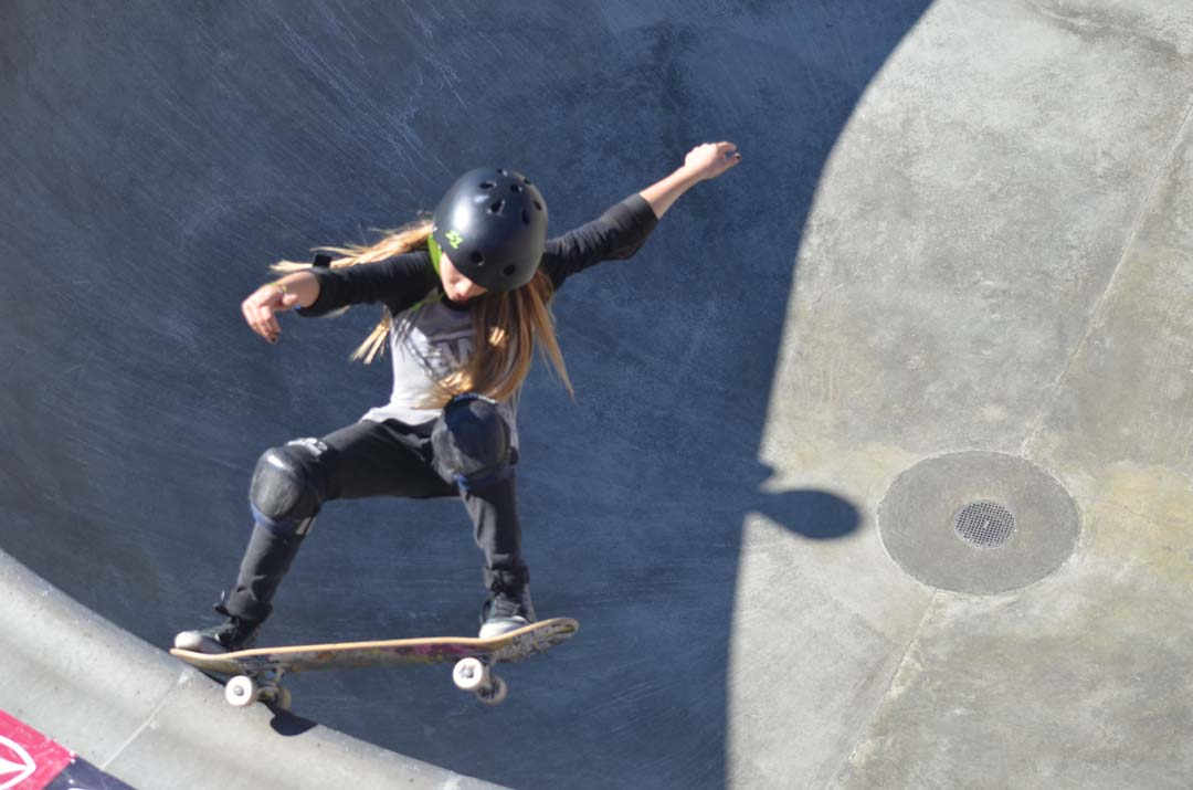 A young skater performs a maneuver in the bowl. Photo by Tony Cagala