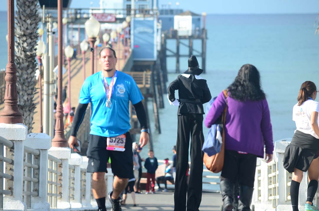 Runners and Anthony LaPugh, the giant pilgrim, cool down at the Oceanside Pier following the race. Photo by Tony Cagala