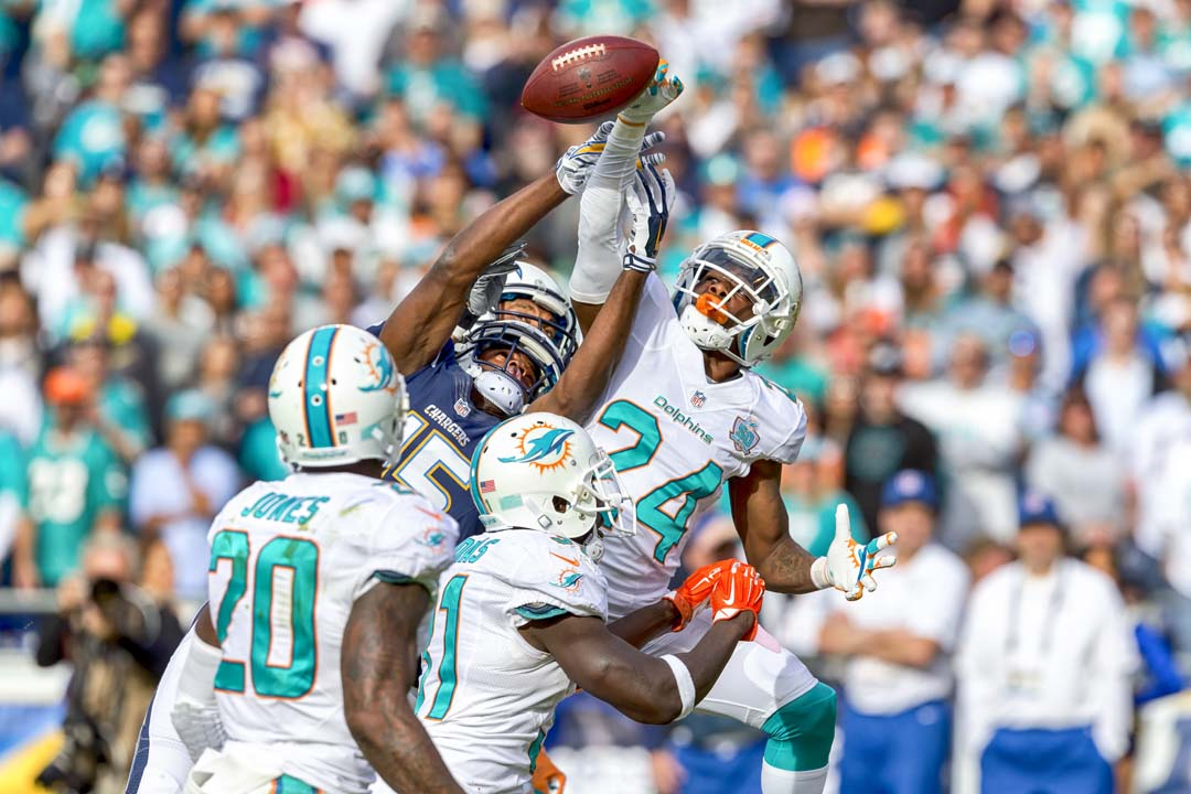 Miami Dolphins cornerback Brice McCain (24) deflects a pass intended for San Diego Chargers wide receiver Dontrelle Inman (15). Photo by Bill Reilly