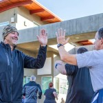 SEALFIT coach Dave Bork, left, high fives runners taking part in the workout of the day. Photo by Bill Reilly