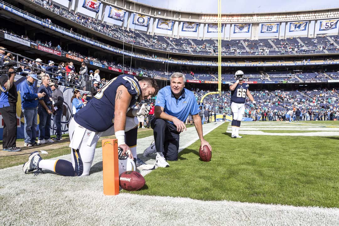 San Diego Chargers Offensive Line Coach Joe D'Alessandris speaks with center Trevor Robinson (60) during pre-game warmups. Photo by Bill Reilly