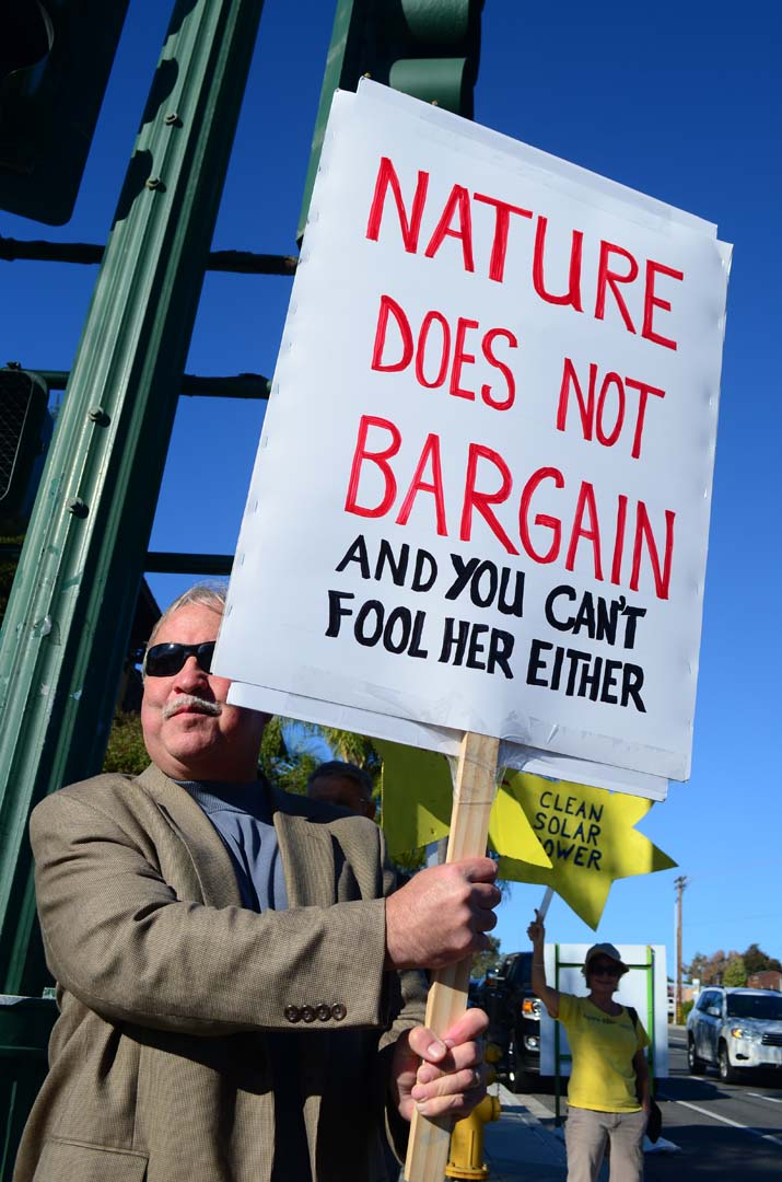 A man holds up a sign at the intersection of Coast Highway 101 and Encinitas Boulevard on Sunday. Photo by Tony Cagala