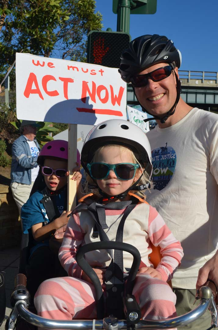 Eloise Wakeham, 3, her dad Chris and brother Miles, 5, ride their bike to the rally on Sunday. Photo by Tony Cagala