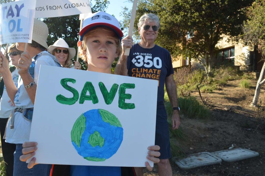 "Palmer Benson, 10, holds a ""Save the planet"" sign up at the rally in Encinitas. Photo by Tony Cagala"