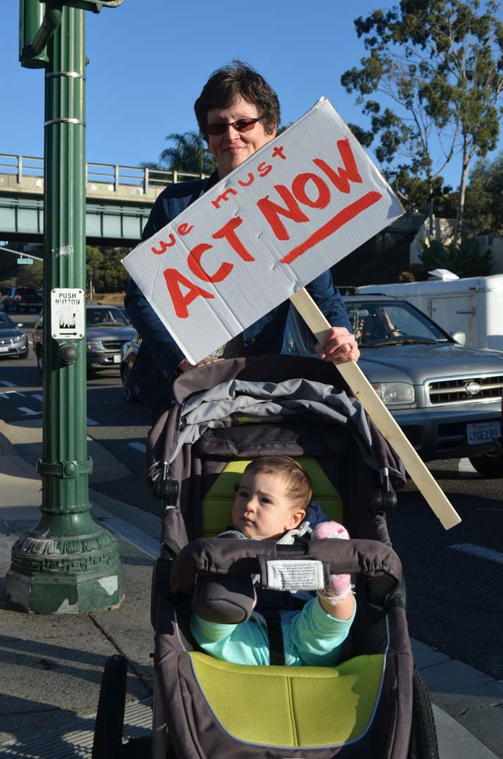 Kim Rice, with 13-month-old granddaughter Kristen Dixon, show support for the climate change talks. Photo by Tony Cagala