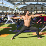 Yoga rock star Alejandro Maldonado assists one of his fans with a yoga pose during a recent class at the Hotel Coral, just north of Ensenada.