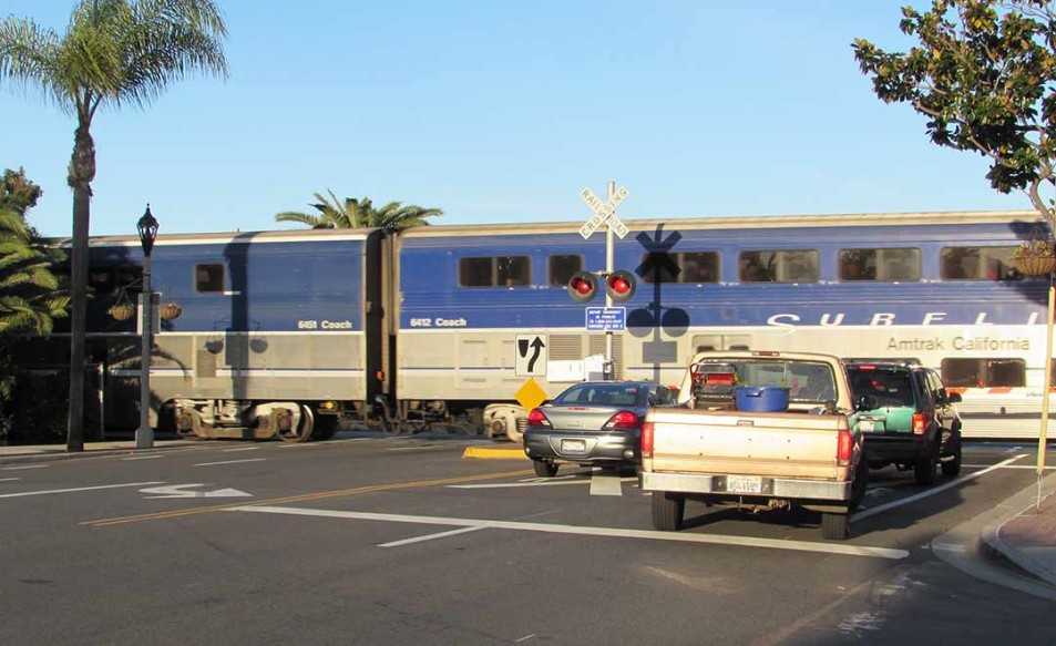 Traffic waits as the Surfliner train rolls by on Carlsbad Village Drive on Monday. The city of Carlsbad is continuing to study the feasibility of trenching the tracks and adding a second line. Photo by Steve Puterski