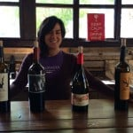 Mara Panentel presents wines ready for tasting at Quinta Monasterio Winery. They include an apricot-peach-pear Chardonnay (Natal), a Merlot, Cabernet Franc and several red blends.
