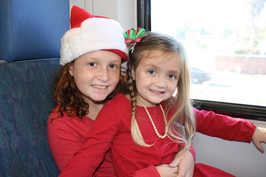 Sisters Sydney Arthur, 9, and Lexi Arthur, 4, of San Marcos, wait for Santa to arrive. Train cars are decorated with window stickers, snowflakes and garland. Photo by Promise Yee