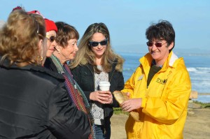 About a dozen or so hopeful whale watchers visit the bluff top lookout at South Ponto State Beach in Carlsbad on Saturday and learn about gray whales and their migratory routes from State Parks officials and volunteers from the San Diego Natural History Museum's naturalist program like Tamara Kurtukova, right. Photo by Tony Cagala