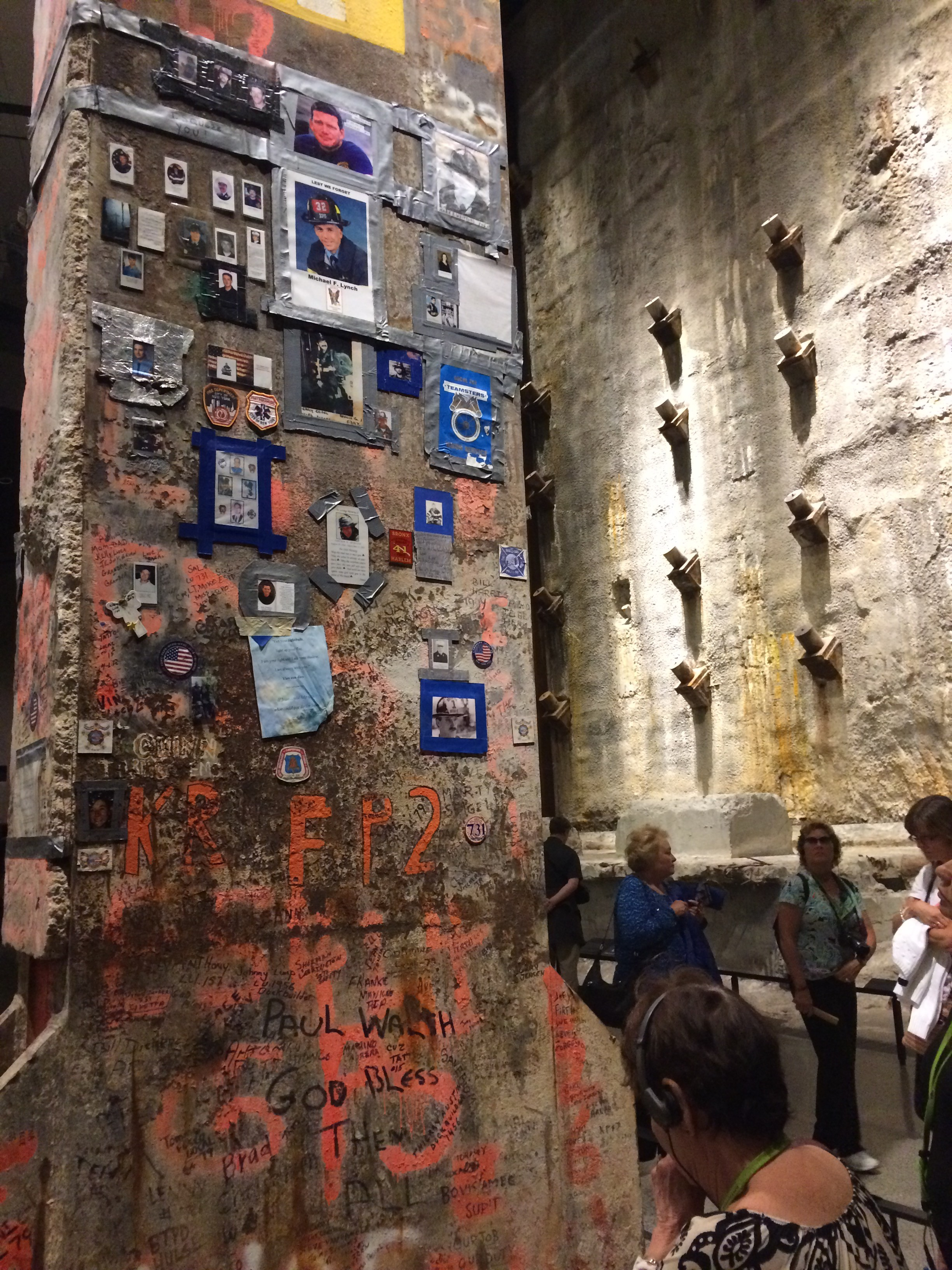 The Last Column is a 58-ton, 36-foot-tall piece of plated steel that was part of the core structure of the World Trade Center's South Tower. It became a makeshift memorial when police, firefighters and other emergency personnel left messages honoring their fallen co-workers. The column is adorned with names, organization stickers, photos, uniform patches and posters.The Last Column is so-named because it was the last- tanding piece of steel during the Ground Zero cleanup. It was stored at Kennedy Airport until 2009 when it was installed in the museum's Foundation Hall. The museum opened May 2014. The slurry wall, to the right, was part of the WTC's foundation. Built to hold back the waters of the Hudson River, it made construction of the towers possible.
