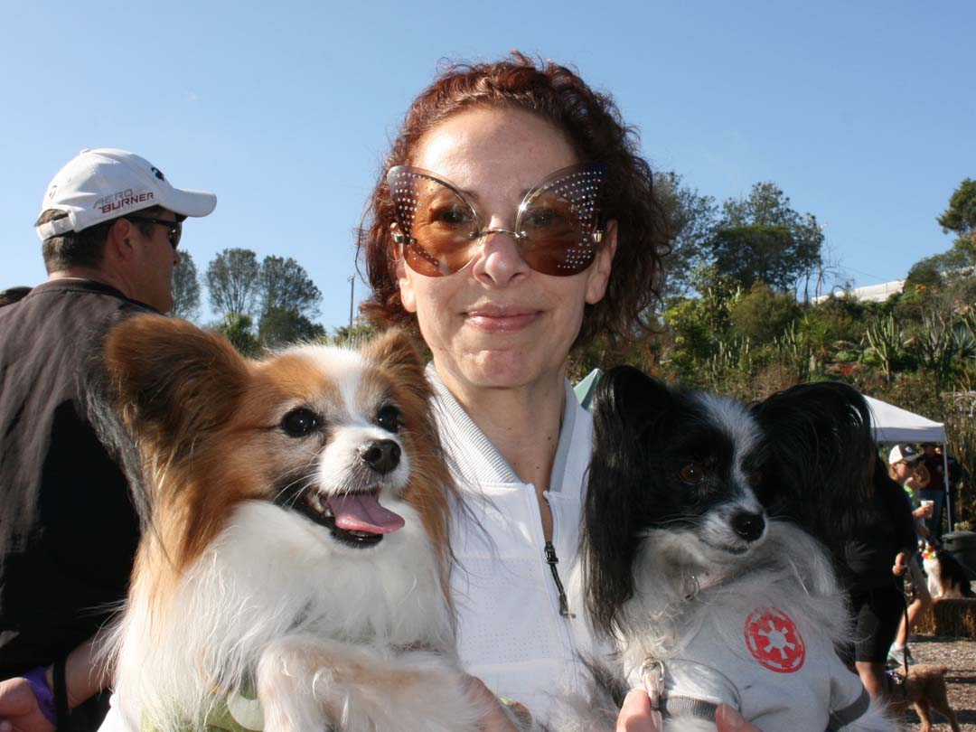 Sara Zaknoen, of Carlsbad, hugs her two papillons. The 5k Paw Walk is a shared fundraiser for San Diego Botanic Garden and Rancho Coastal Humane Society. Photo by Promise Yee