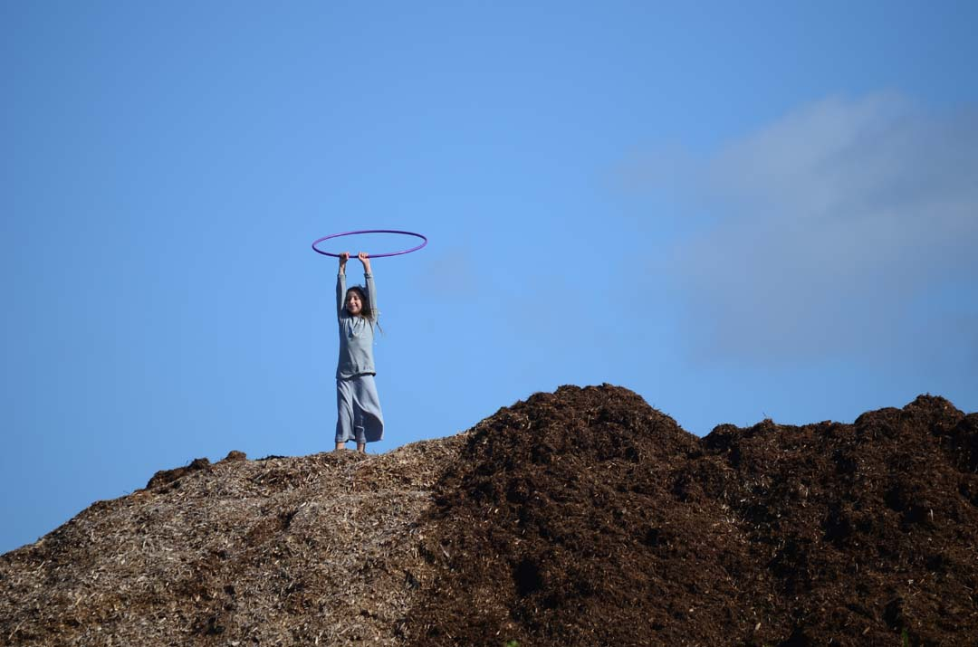 A youngster finds some fun with a hula hoop atop a mound of compost. Photo by Tony Cagala