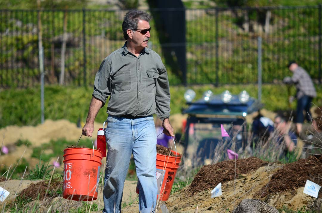 Arturo Padilla carries buckets of compost to spot for planting trees. Photo by Tony Cagala
