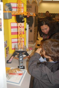 """Attendees check out the food crane, built by kindergartener Pete McNamara for those who """"don't want to get up and get the food."""" Photo by Bianca Kaplanek"""